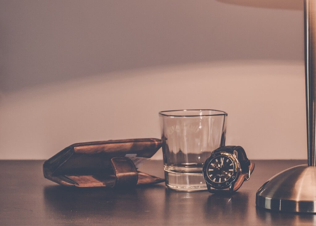 テーブルの上に置かれた財布とグラスと腕時計