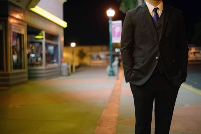 スーツを着て街に立っている男性