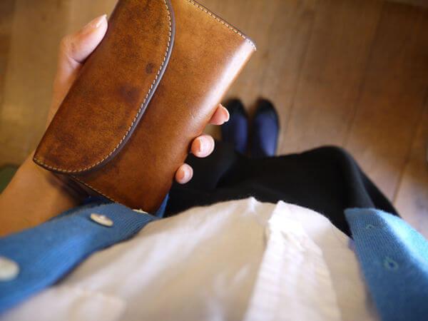 ホワイトハウスコックスの三つ折り革財布を手で持っている男性